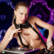 Sexy young blonde lady DJ in suspenders playing music at night c - Stock Photo