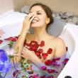 Stock Photo: Happy woman in a bath with rose-petals